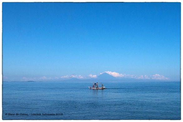 Fishermen cast their nets, off the coast of Lombok, Indonesia. In the distance volcano Gunung Anung on the island Bali. | March 2015