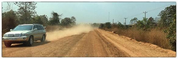 En ook dit is Cambodja. Als de wind gunstig staat, zoals nu, heb je niet veel last van het stof. Komt de wind van de andere kant, of is het windstil, zit je in no time stof te happen. Je kunt geen kant uit, dus laat maar over je heen komen.
