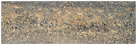 Nu wordt het ernstig. 'n Soort grof bitumen met uitpuilende brokjes steenslag, het grijpt je banden vast, het kost je zomaar 30% meer inspanning om je wielen te laten draaien. Oppassen ook bij de randen: doorgaans slecht afgewerkt, groot niveauverschil, voor je het weet schiet je in de berm.