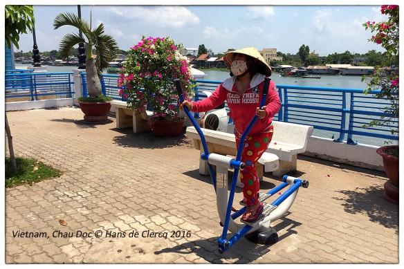 VIETNAM - En deze dame, die bij 38°C aan haar conditie werkt op een een van de publieke crosstrainer die langs de Mekong op de boulevard staan. Petje af! Geen land waar ze zo beweeglijk zijn als Vietnam.