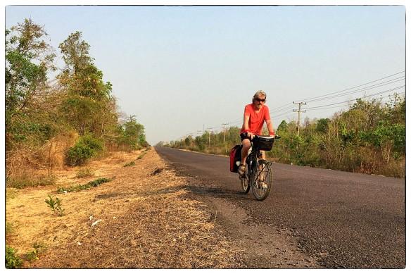 LAOS - Soms moet je een zelfportret maken, zien wat anderen zien: een eenzame man op z'n fiets. Heel gedoe nog, met zelfontspanner en de camera zo plaatsen dat een voorbijrijdende auto hem niet omverblaast. Dan is zo'n doodstille weg wel handig.