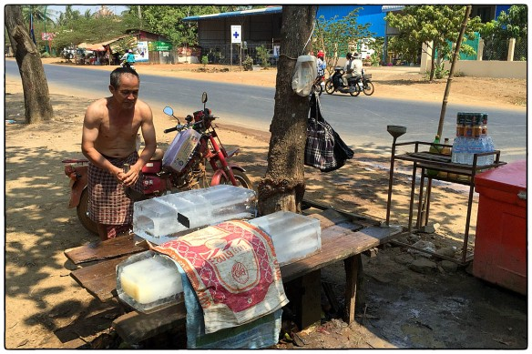 CAMBODJA - In een land waar winkeliers geen koelkast hebben maar een koelbox, wordt ijs verhandeld. Dit is de tussenhandelaar. Hij koopt staven ijs en maakt er handzame blokken van. Blijft een bizar gezicht, bij 40℃.
