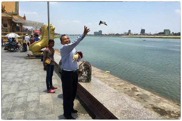 CAMBODJA - Het vrijlaten van vogels is goed voor je karma, denken boeddhisten, en daar spelen handelaars graag op in. Twee vogels voor een dollar. Deze man kocht zo'n beetje de hele vogelkooi leeg. Iedereen blij, vooral de vogels.