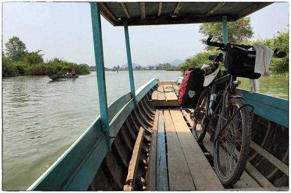 LAOS - Met een bootje naar een eiland in de Mekong. Rustig tuffen, wind om je oren, en de fiets staat stevig verankerd in de houten vlonder. Soms is geluk heel eenvoudig.