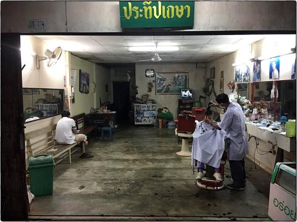 Thailand. Tien uur 's avonds, de kapper nog steeds aan het werk. Zijn klant: een jochie. Nog lang geen bedtijd.