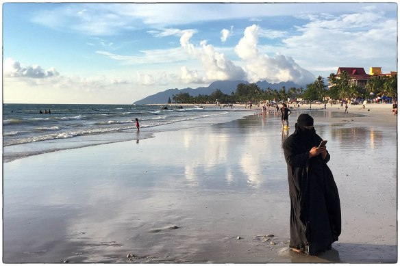 Maleisië, op het eiland Langkawi. Brievenbusvrouwtjes, noemen Mirjam en ik de in zwart gehulde moslimas die de wereld door een spleetje zien. Wat zou ze doen, hier aan het strand? Een duik nemen kan niet met al die kleren. Een sms'je dan maar? Niet aan haar man, die dobbert lekker in de golven, in z'n zwembroek.