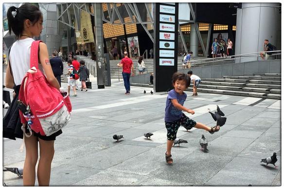 Singapore. Klein rotjoch verkoopt de duiven een schop als ze in de buurt komen. Zusje kijkt bedenkelijk, maar laat het ettertje z'n gang gaan.