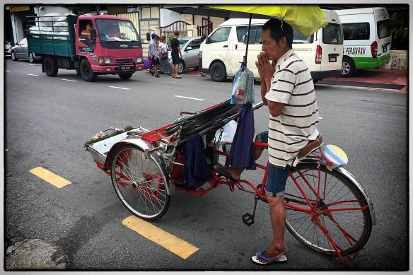Maleisië. Op het eiland Penang doet de riksjafietser een schietgebedje. Voor klandizie? Zou er een riksjagod zijn? In India is dat Ganesh, beschermheilige van reizigers. Maar hier?