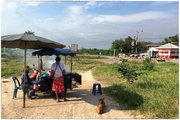 Dit is nu écht street food. Zomaar ergens langs de weg in Thailand, bij een spoorwegovergang, lijkt een strategische plek. Maar waarom zetten ze die parasol niet strategischer neer? Zodat ze in de schaduw kunnen staan? Nu staat er één krukje. Voor die klant die straks komt. Hopelijk.