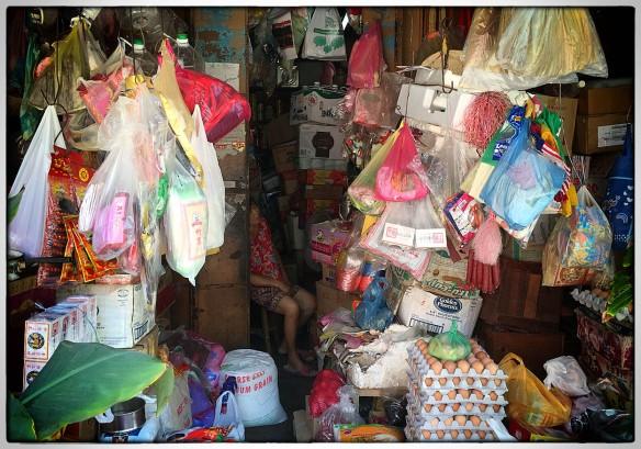 Maleisië, Georgetown. Een tijdje naar haar staan kijken, maar geen beweging. Uitgeput van het inventariseren? Proberen orde te scheppen in chaos? Nauwelijks ruimte voor haar krukje, zo vol is de winkel.